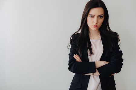 Young attractive emotional girl in business-style clothes on a plain white background in an office or audience alone Imagens - 133458665