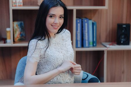 Young emotional attractive girl sitting at a desk in a modern office or auditorium alone Imagens