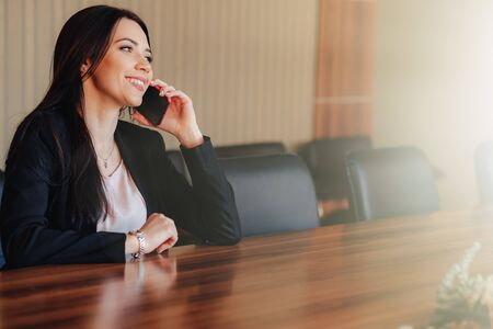 Young attractive emotional girl in business style clothes sitting at desk with phone in office or audience alone Imagens - 133458765