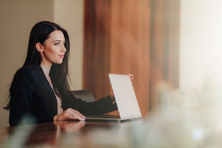 Young attractive emotional girl in business-style clothes sitting at a desk on a laptop and phone in the office or auditorium alone Imagens - 133458766