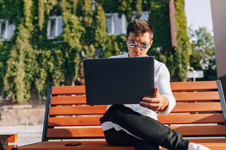young stylish guy in white shirt with phone and notebook works on bench on sunny warm day outdoors, freelance Imagens - 133458769