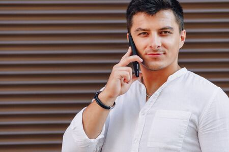 young stylish guy in shirt talking by phone on simple brown background Imagens - 133458771