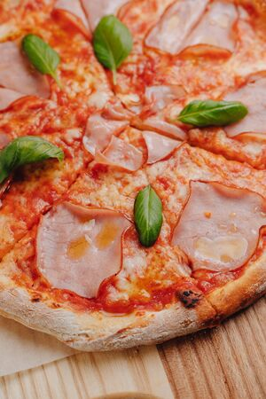 Neapolitan pizza on a cream sauce with ham, cheese, arugula, basil, tomatoes sprinkled with cheese on a wooden board on a tablecloth in a cell with a place for text