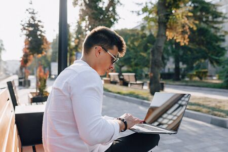 young stylish guy in white shirt with phone and notebook works on bench on sunny warm day outdoors, freelance Imagens - 133458970
