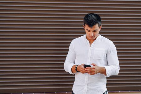 young stylish guy in shirt typing on phone on simple brown background Imagens