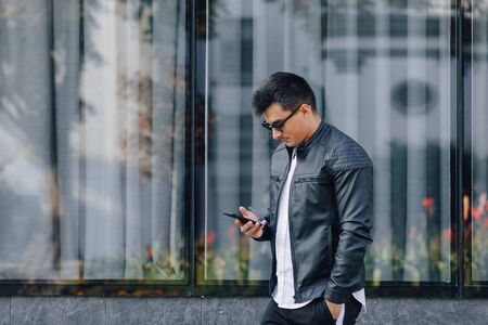 young stylish guy in glasses in black leather jacket with phone on simple glass background Imagens - 133458978