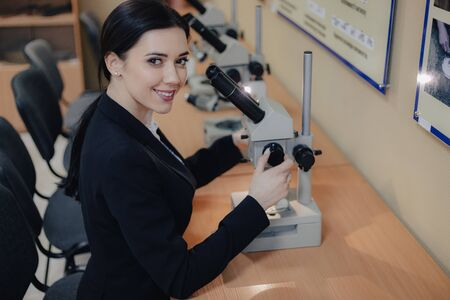 Young emotional attractive girl sitting at the table and working with a microscope in a modern office or audience alone Imagens - 133458982