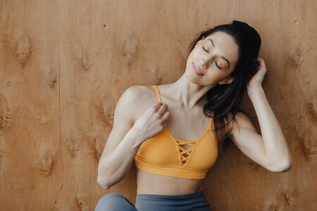 Young attractive fitness girl sitting on the floor near the window on the background of a wooden wall, resting on yoga classes at gym Imagens - 133458983