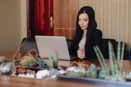 Young attractive emotional girl in business-style clothes sitting at a desk on a laptop and phone in the office or auditorium alone Imagens - 133458987