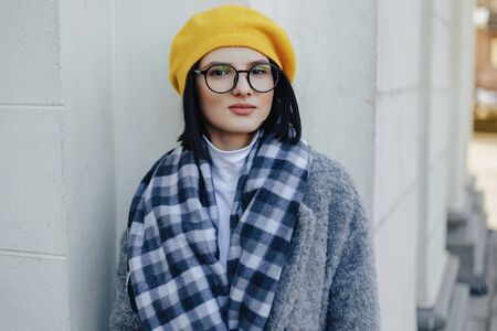 Attractive young girl in stylish glasses in coat and yellow Beret on a simple light background Imagens - 133458988