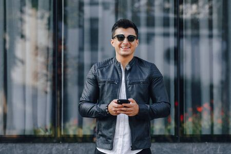 young stylish guy in glasses in black leather jacket with phone on simple glass background Imagens - 133459019