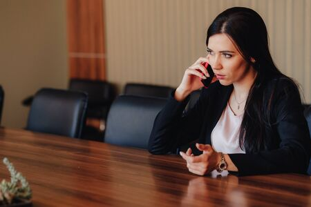 Young attractive emotional girl in business style clothes sitting at desk with phone in office or audience alone Imagens - 133459020