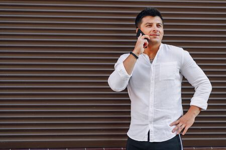 young stylish guy in shirt talking by phone on simple brown background Imagens - 133459056