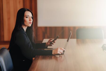 Young attractive emotional girl in business-style clothes sitting at a desk on a laptop and phone in the office or auditorium alone Imagens - 133459114