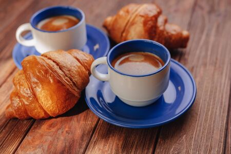 two cups of hot coffee and croissants on a wooden background, good light, morning atmosphere Imagens