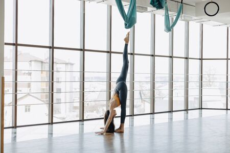 cozy young attractive girl doing fitness exercises with yoga on the floor against the background of panoramic windows