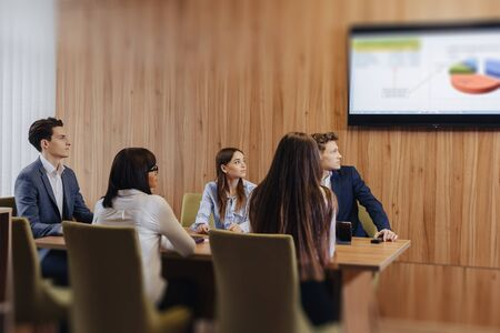 large team of people is working like team at one table for laptops, tablets and papers, on the background a large TV set on a wooden wall Imagens - 133459149