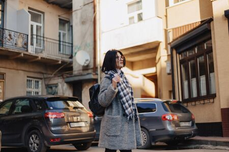 Attractive positive young girl wearing glasses in a coat on the background of buildings on cars on sunny day Imagens - 133459151