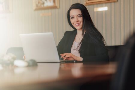 Young attractive emotional girl in business-style clothes sitting at a desk on a laptop and phone in the office or auditorium alone Imagens - 133459176