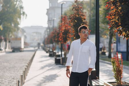 young stylish guy in a white shirt walking down a European street on a warm sunny day