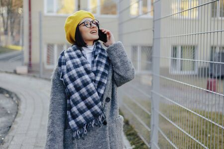 An attractive young girl wearing sunglasses in a coat and a beret walking down the street and talking on the phone and smiles Imagens