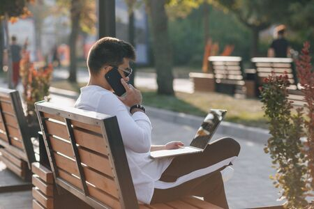 young stylish guy in white shirt with phone and notebook works on bench on sunny warm day outdoors, freelance Imagens - 135055000