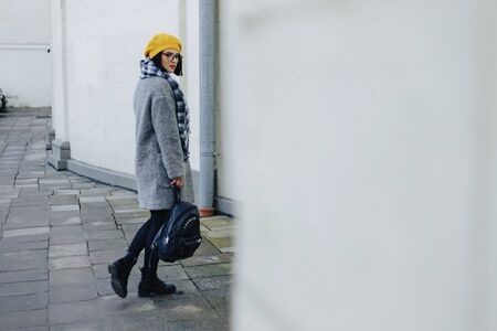 Attractive young girl in stylish glasses in coat and yellow Beret freestyle walking Imagens