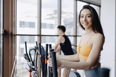 young attractive girl at gym on exercise bike, fitness and yoga training Imagens - 135054928