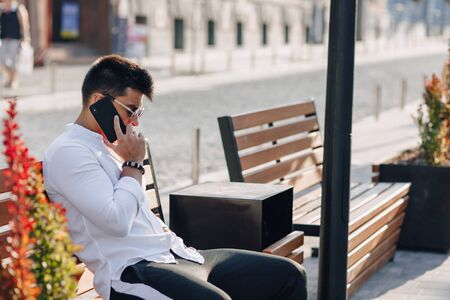young stylish guy in white shirt with phone on bench on sunny warm day outdoors Imagens - 135054988