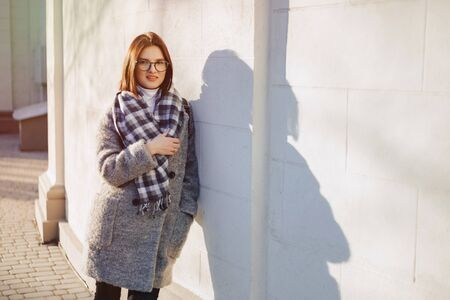 Attractive young girl wearing glasses in a coat on a urban background walking on a sunny day Imagens - 135054990