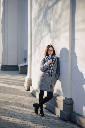 Attractive young girl wearing glasses in a coat on a urban background walking on a sunny day Imagens - 135055239