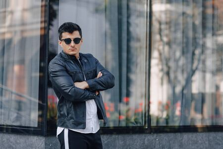 young stylish guy in glasses in black leather jacket on simple glass background Imagens - 135055133