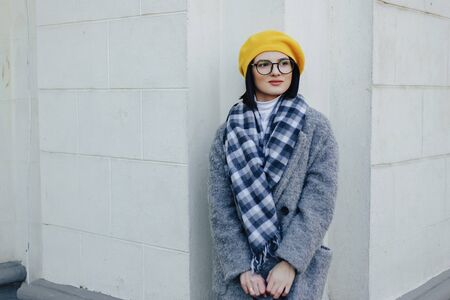 Attractive young girl in stylish glasses in coat and yellow Beret on a simple light background Imagens - 135057201