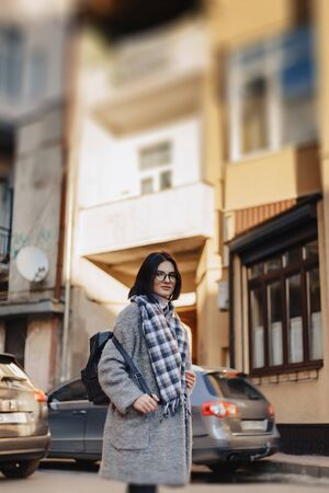 Attractive positive young girl wearing glasses in a coat on the background of buildings on cars on sunny day Reklamní fotografie