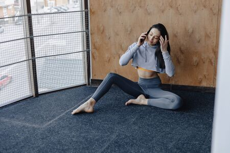 Young attractive fitness girl sitting on the floor near the window on the background of a wooden wall, resting on yoga classes at gym and talking on phone Imagens - 135057165