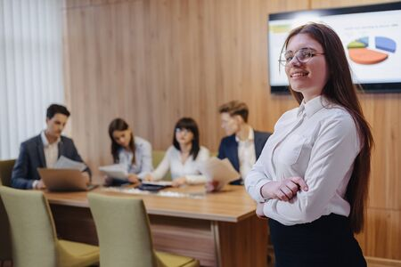 young attractive stylish office worker girl in glasses with a notebook in the hands on blurry background of working colleagues Imagens - 135056938