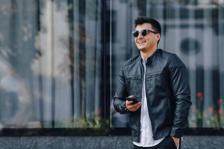 young stylish guy in glasses in black leather jacket with phone on simple glass background Imagens - 135056927