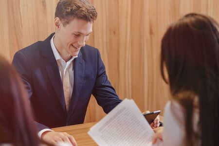 A stylish young man in a jacket and shirt sits at the desk with his colleagues and works with documents at office Imagens