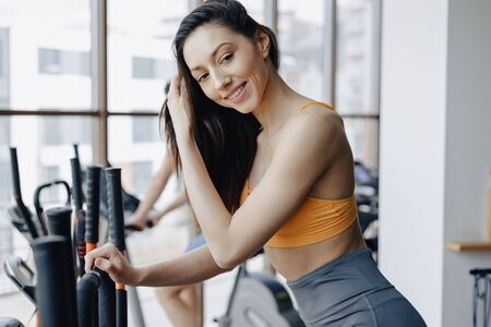 young attractive girl at gym on exercise bike, fitness and yoga training