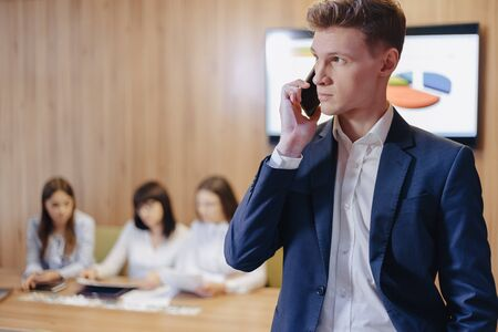 Stylish young businessman wearing a jacket and shirt on the blurry background of a working office with people talking on a mobile phone Imagens - 135057207