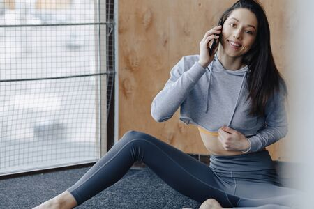 Young attractive fitness girl sitting on the floor near the window on the background of a wooden wall, resting on yoga classes at gym and talking on phone Imagens - 136144162