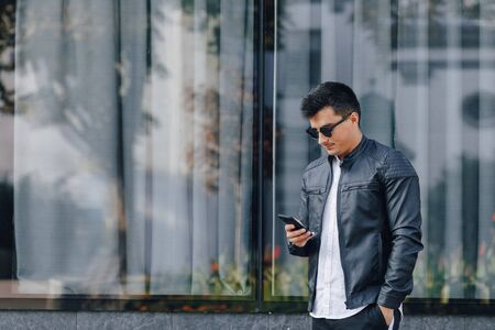 young stylish guy in glasses in black leather jacket with phone on simple glass background Imagens - 135057123
