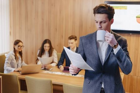 A stylish young man in a jacket and a shirt with a cup of coffee in his hand stands and reads documents on the background of working colleagues at office Imagens