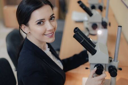 Young emotional attractive girl sitting at the table and working with a microscope in a modern office or audience alone Imagens
