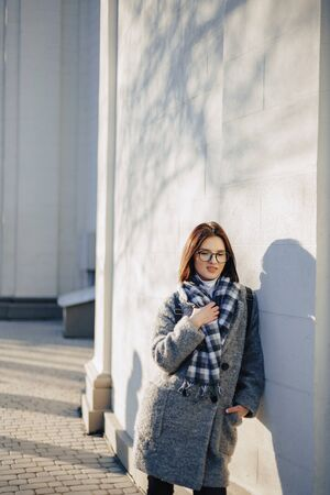 Attractive young girl wearing glasses in a coat on a urban background walking on a sunny day Imagens - 135204157