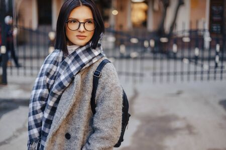 Attractive young girl wearing glasses in a coat on a urban background walking on a sunny day Imagens - 135204205