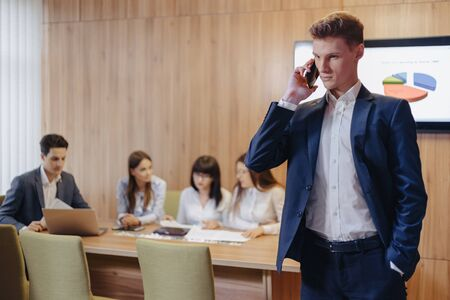 Stylish young businessman wearing a jacket and shirt on the blurry background of a working office with people talking on a mobile phone Imagens