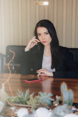 Young attractive emotional girl in business style clothes sitting at desk with phone in office or audience alone Imagens - 136393016