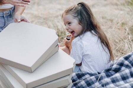 little girl having fun at picnic, eating pizza, drinks, summer and lawn Imagens