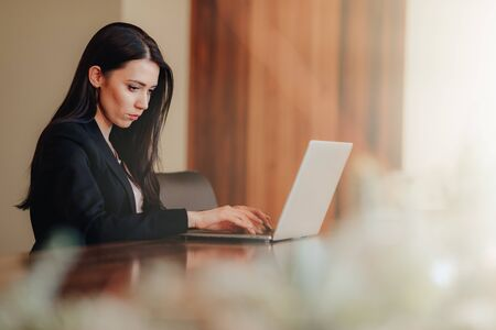 Young attractive emotional girl in business-style clothes sitting at a desk on a laptop and phone in the office or auditorium alone